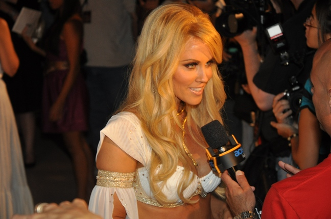 Jenny McCarthy, white bikini top with gold trim, gold snake necklace, gold arm bands
