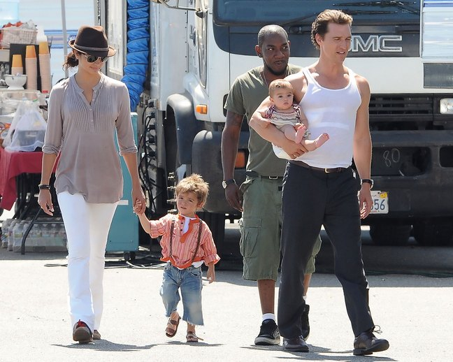 Matthew McConaughey, white tank top, black dress pants, Camila Alves, white pants, brown fedora, beige shirt, bracelets