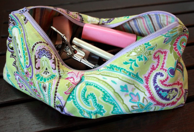 a green paisley makeup bag with assorted makeup inside