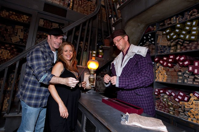Kelly Preston, black dress, John Travolta, black baseball hat, jeans, flannel shirt, Wizarding World of Harry Potter