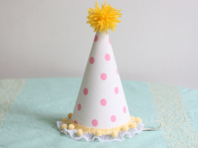 a homemade party hat with pink polka dots and a yellow pom pom