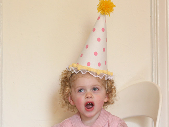 a smiling child with the homemade party hat on her head