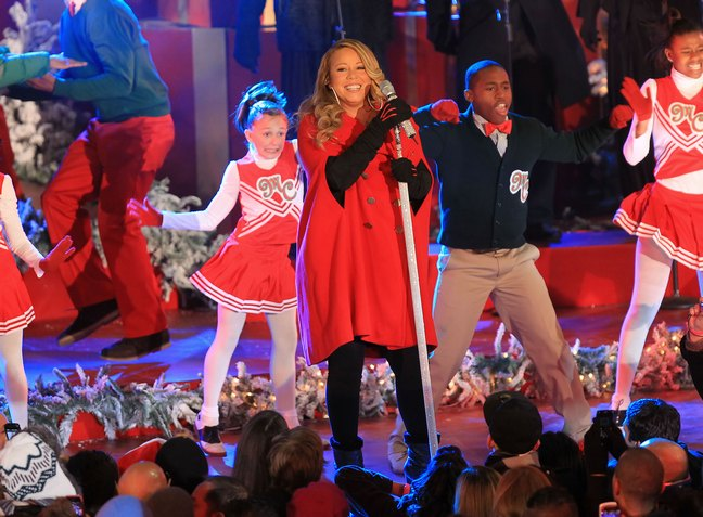 Mariah Carey, red christmas outfit, rockefeller center, black boots, black  pants, - Pregnant Mariah Carey Films Christmas Special