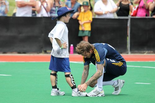 david beckham ties shoes, david beckham blue shorts, blue shirt