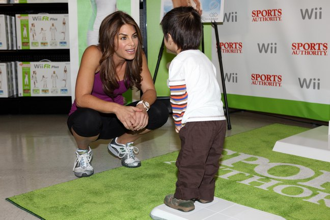 Jillian Michaels, purple tank top, black leggings, tennis shoes