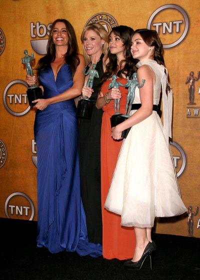 Sofia Vergara blue dress, Julie Bowen black pantsuit, Ariel white dress, Sara orange dress