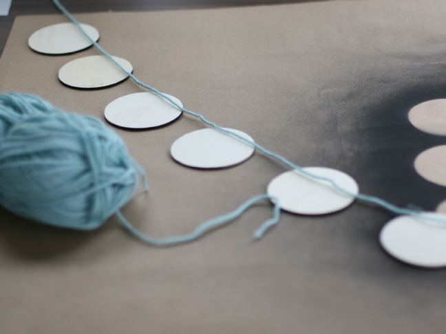 stringing blue yarn across white disks