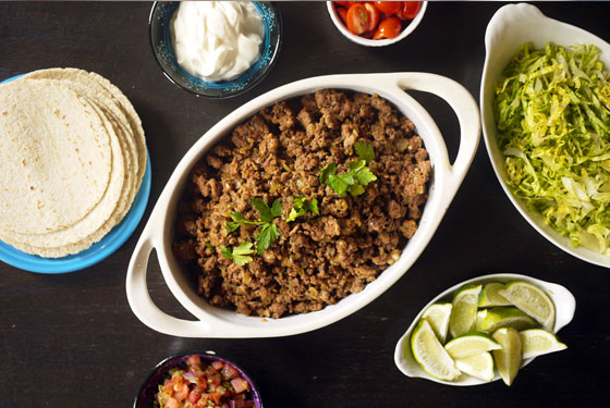 taco meat in a white dish tortillas shredded lettuce