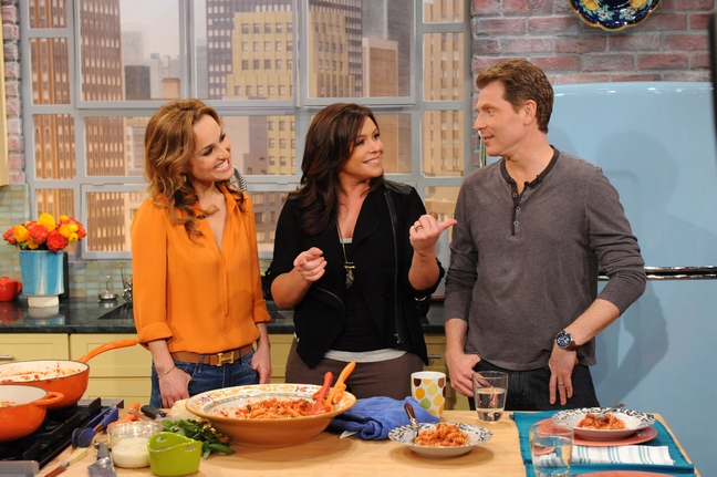 Giada Laurentiis and Bobby Flay smiling at Rachel Ray in a busy kitchen on her show