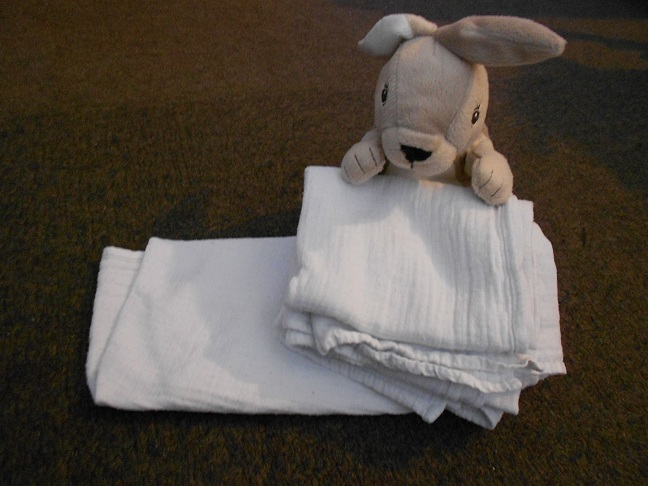 a stack of muslin cloth squares with a baby toy in the back