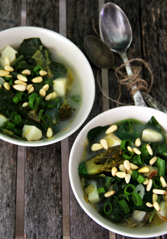 Green Superfood soup in a white bowl topped with pine nuts