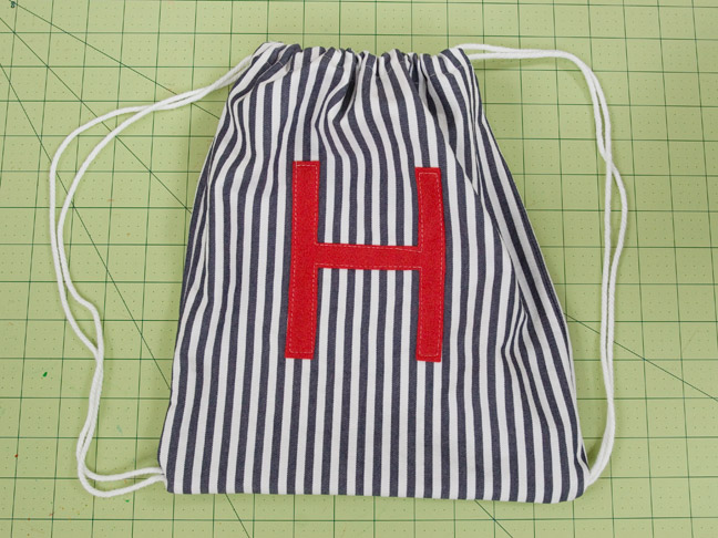 the homemade blue pinstriped backpack with the felt letter on the front