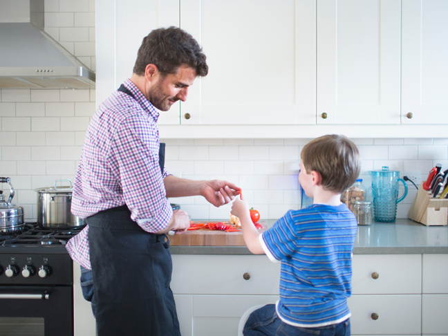 father-son-chopping-tomatoes-kitchen