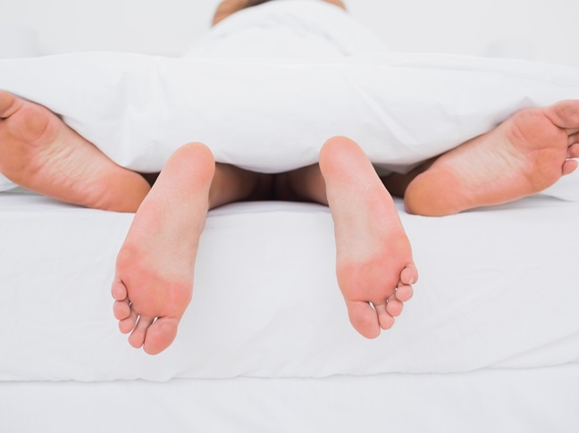 Couple laying in the sheets in bed