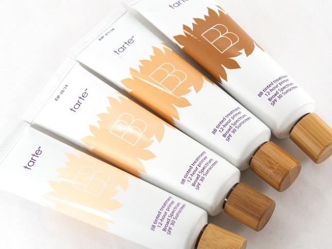 4 small white tubes of tarte bb cream with wooden covers laying side by side