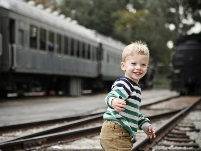 a little blonde boy smiles and runs along the train track