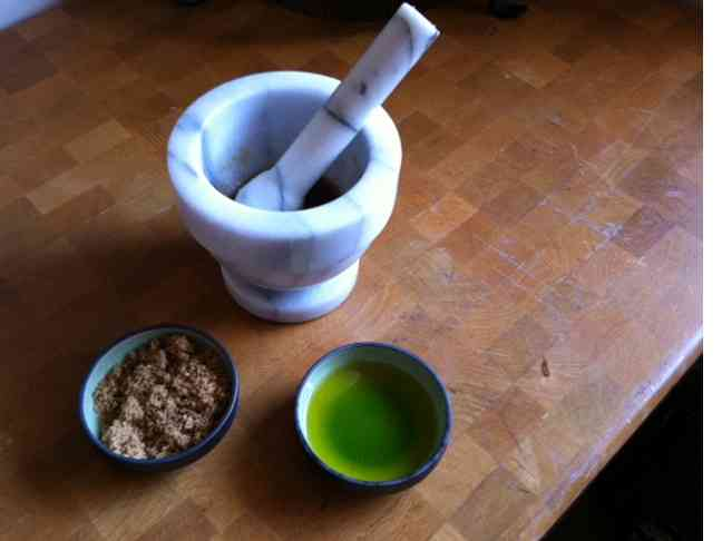 mortar and pestle pictured with bowls of sugar and olive oil