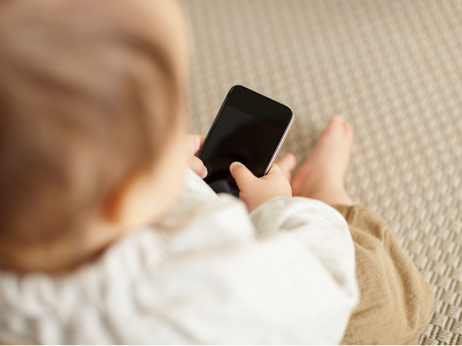 a baby sitting on the carpet holding a iphone