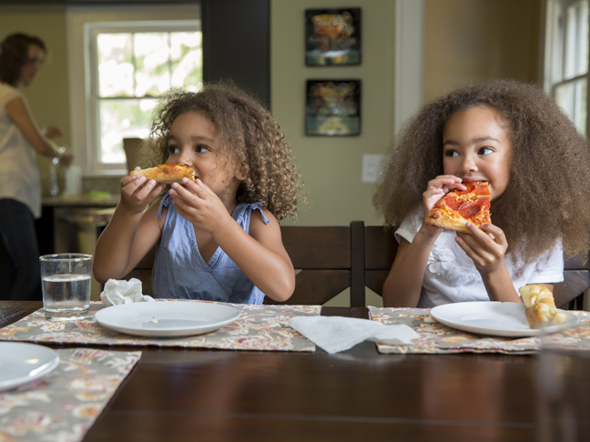 two young girls eating pizza at a table