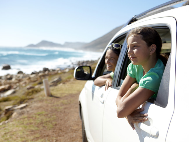 girl-looking-out-car-window-at-ocean