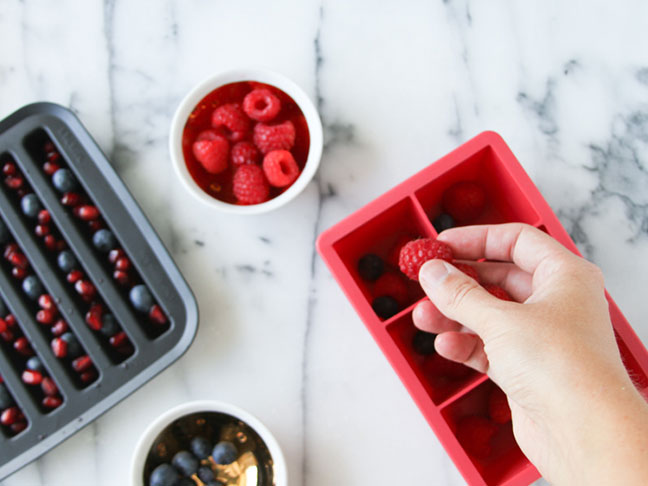 Add raspberries, blueberries, and pomegranate to ice cube trays
