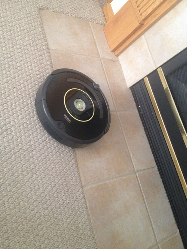 black irobot roomba on tile and carpet