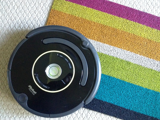 iRobot roomba closeup cleaning a rainbow carpet