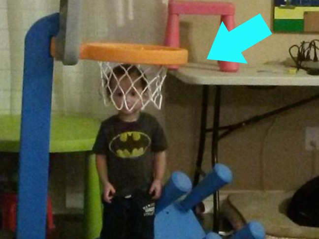 child trying to hide in a basketball hoop
