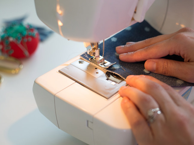 sewing-machine-hands-polka-dot-denim-fabric