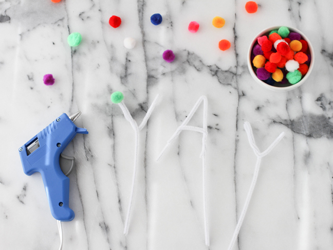 gluing pom poms to pipe cleaners
