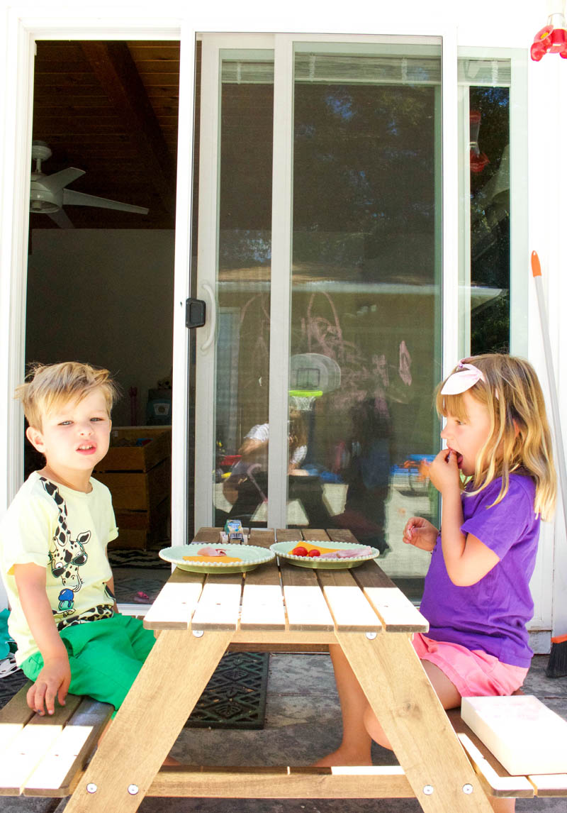 kids eating dinner at picnic table