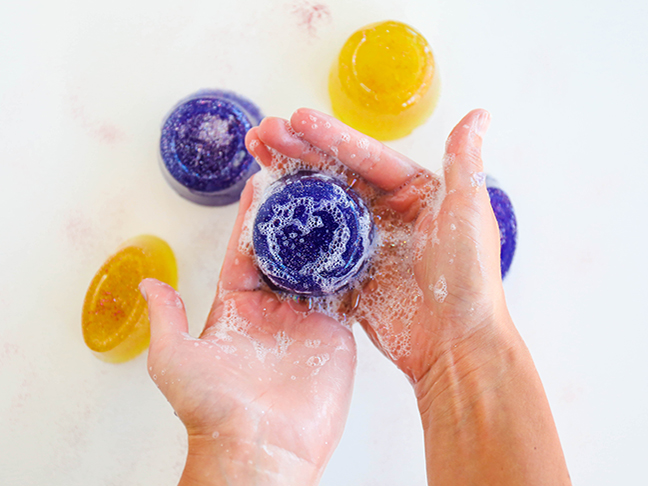hands holding soapy purple round soap