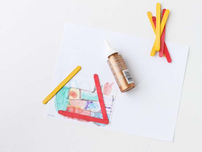 Add glue to popsicle sticks to create frame