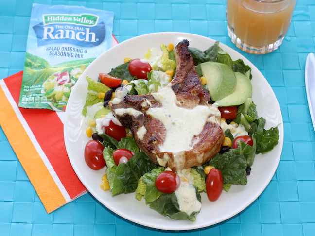 pork chop on top of green salad with tomatoes