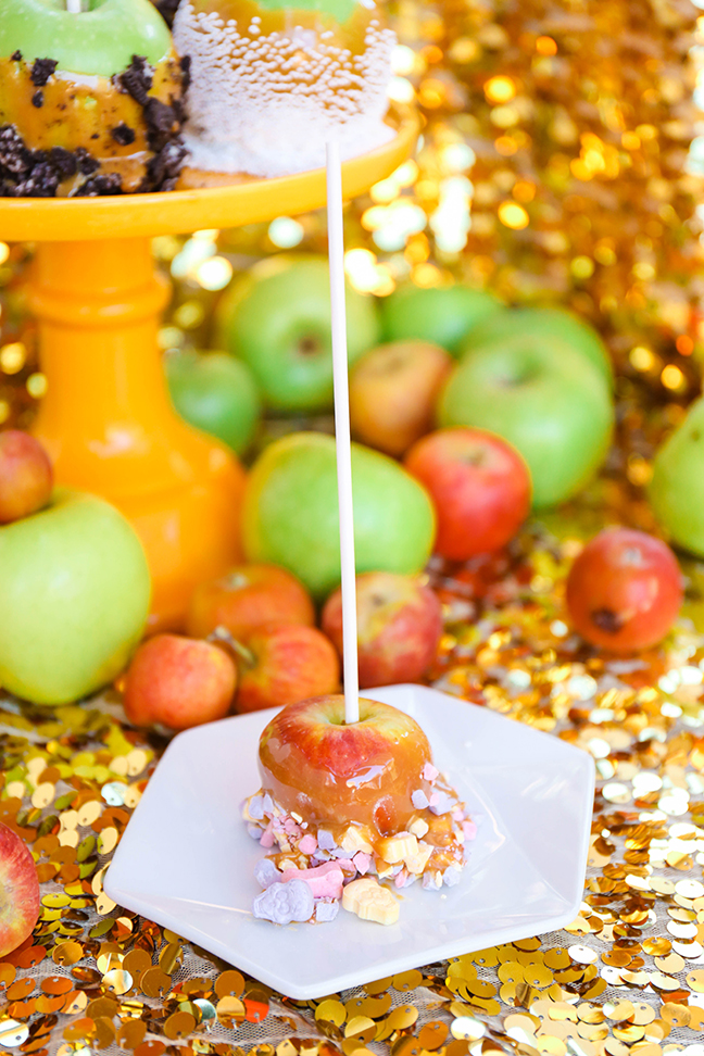 caramel apple dipped in sweetarts on white plate