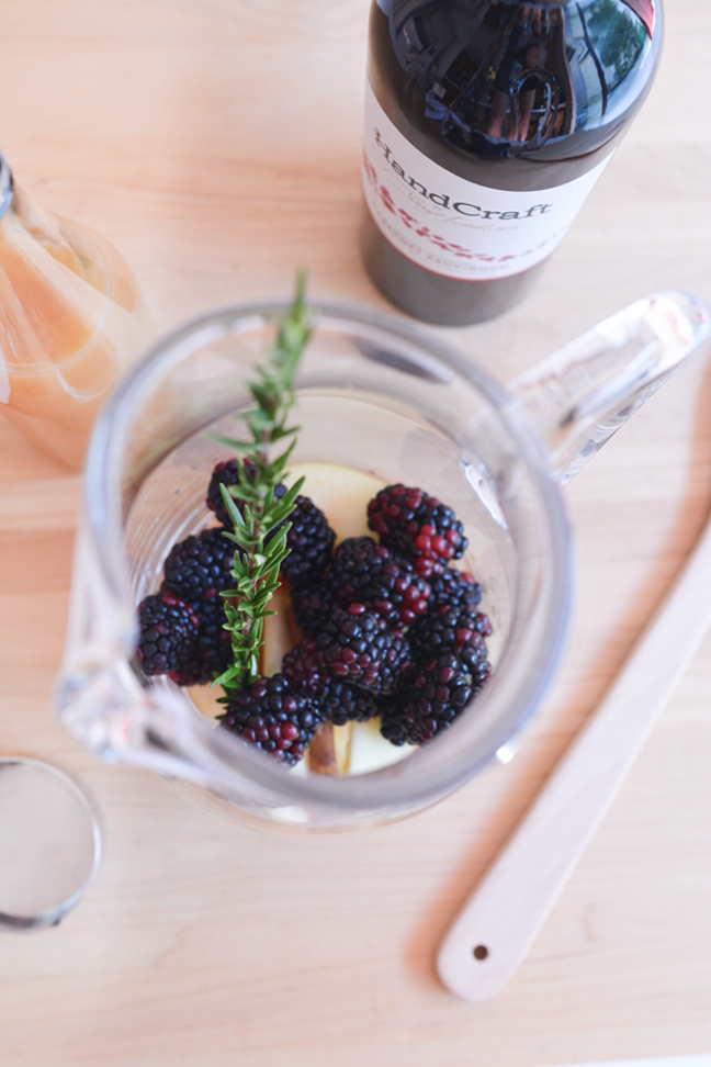 blackberries and rosemary sprig in glass pitcher