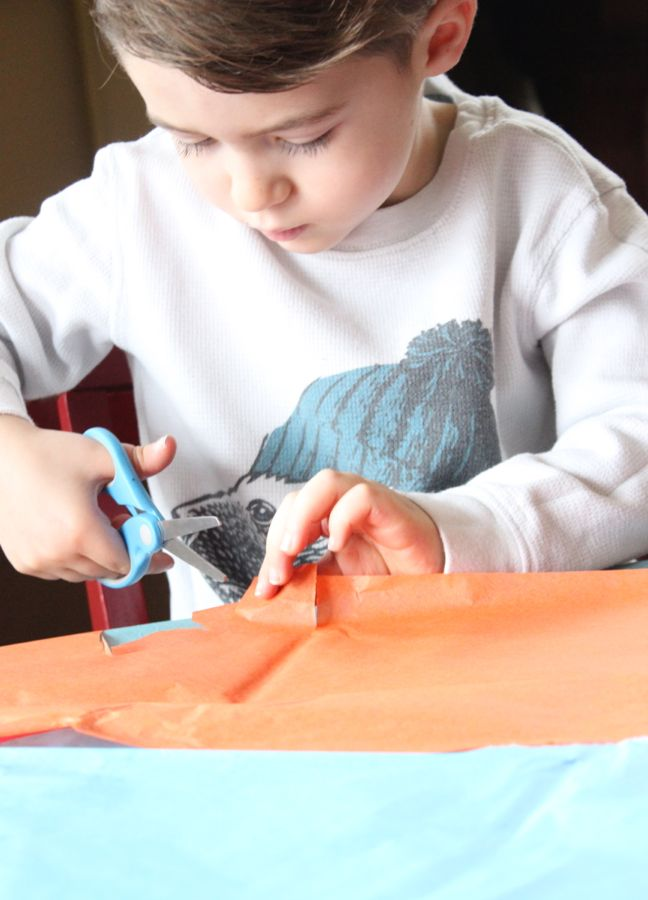 boy-cutting-tissue-orange-tissue-paper