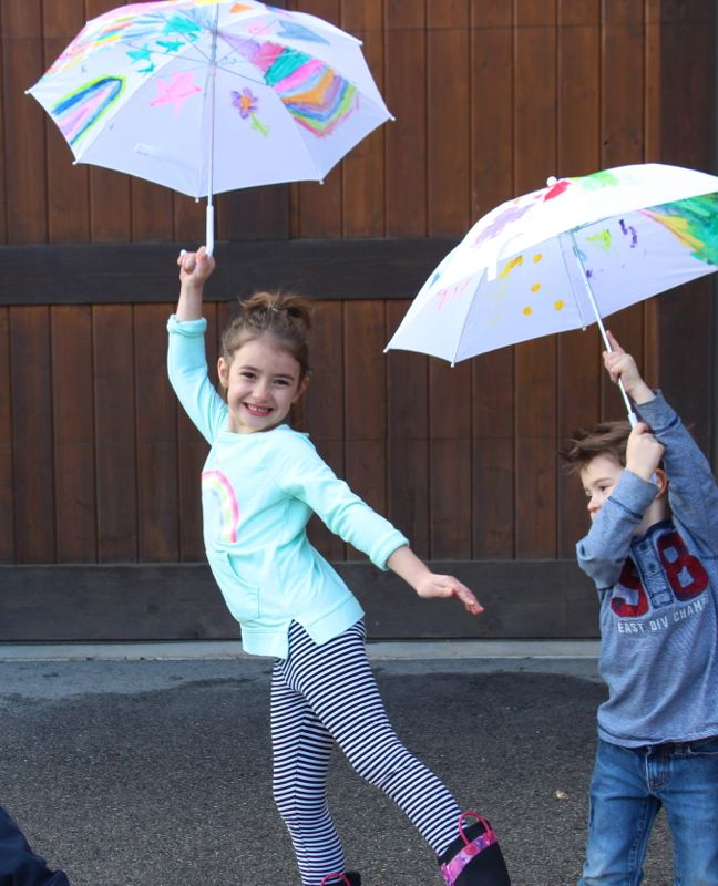 kids holding painted umbrellas