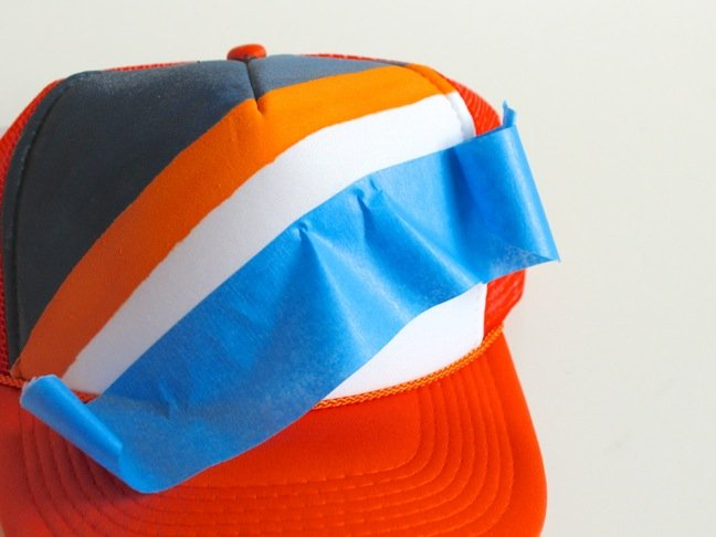 orange-and-blue-truckers-hat-with-blue-painters-tape