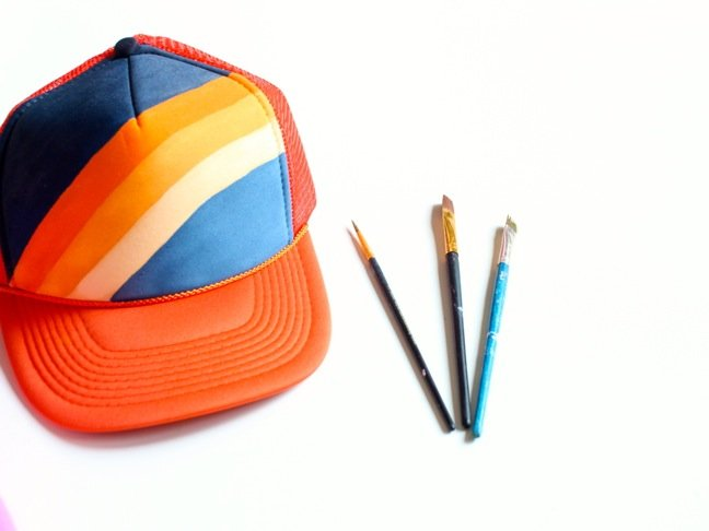 trucker-hat-with-orange-and-blue-rainbow-and-paintbrushes