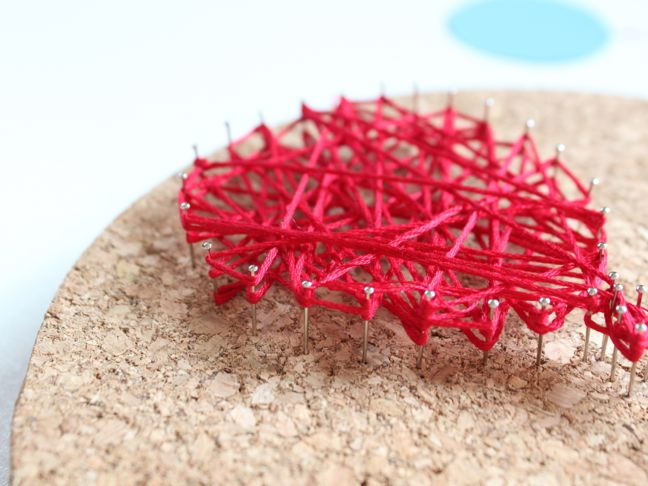 red-string-wrapped-around-pins-in-cork