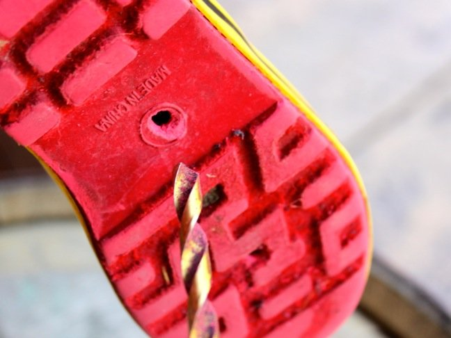 drill-a-hole-in-the-bottom-of-a-shoe-with-a-red-sole