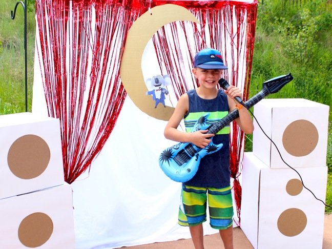 boy-wearing-a-hat-and-holding-a-guitar-siniging-on-a-microphone-with-a-diy-mini-stage