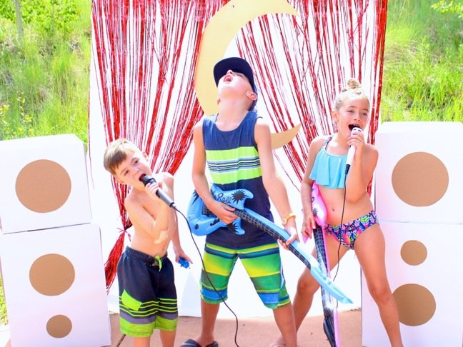kids-in-swim-suits-singing-on-a-diy-mini-stage-with-microphones